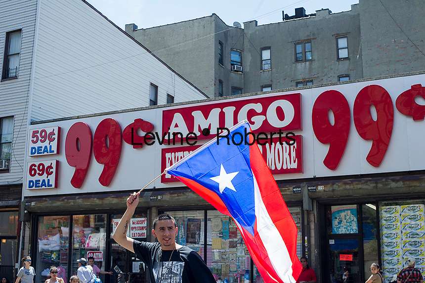 A parade goer waves a Puerto Rican flag at The Brooklyn Puerto Rican Day Parade in the Bushwick neighborhood of Brooklyn in New York on Sunday, June 2, 2013. As more and more hipsters move into the neighborhood the ethnicity of the area is changing.   (©Frances M. Roberts)