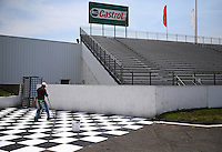 May 29, 2013; Englishtown, NJ, USA: A man touch up paints a checkered flag in the winners circle at Raceway Park. Mandatory Credit: Mark J. Rebilas-
