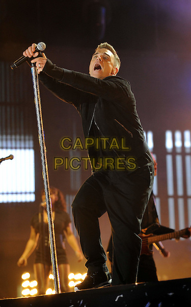 ROBBIE WILLIAMS.The Heroes Concert in aid of the charity Help For Heroes, Twickenham Stadium,  London, England. .September 12th, 2010.stage concert live gig performance music full length black shirt jacket jeans denim mouth open dancing .CAP/WIZ.© Wizard/Capital Pictures.
