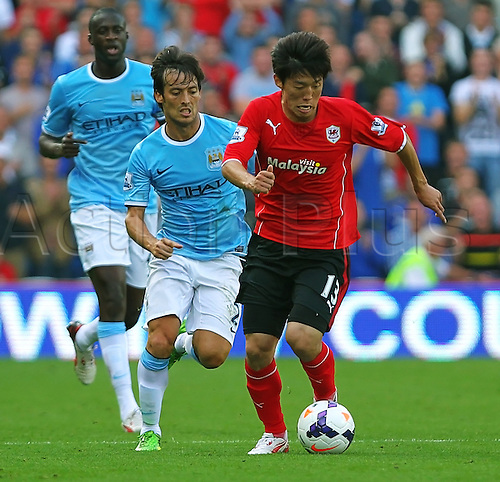 25.08.2013 Cardiff, Wales. Kim Bo-Kyung of Cardiff City runs with the ball during the Premier League fixture between Cardiff City and Manchester City from the Cardiff City Stadium.