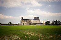 The Port of New York Grain Elevator Terminal in the neighborhood of Red Hook in New York is seen from the softball fields of Red Hook Park during City Of Water Day on Saturday, July 20, 2013. The grain elevator was originally part of the NYS Barge Canal and was built in 1922 and is now part of the GBX-Gowanus Bay Terminal and is used for video and movie shoots. Future uses are considered for the storage of cement. The City of Water Day reconnects New Yorkers with the waterfront offering opportunities to see industrial uses as well as recreational uses. (© Richard B. Levine)