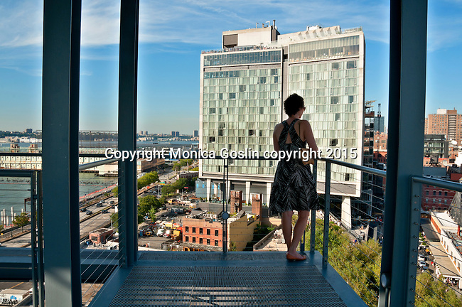 A woman looks out at the view of the city and The Standard Hotel, as seen from one of the outdoor terraces at the Whitney Museum of American Art
