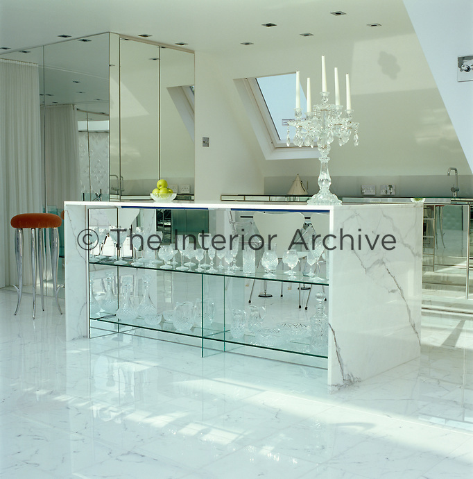 Glass, mirror and marble surfaces in the kitchen area reflect the light in the penthouse