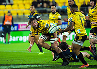 Liam Mitchell passes to Ngani Laumape during the Super Rugby match between the Hurricanes and Highlanders at Westpac Stadium in Wellington, New Zealand on Friday, 1 March 2019. Photo: Dave Lintott / lintottphoto.co.nz
