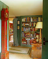 An antique grandfather clock stands against one wall of the entrance hall whilst the wall opposite is entirely lined with bookshelves