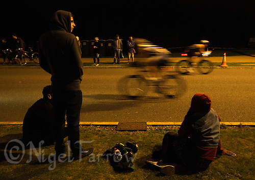 16 AUG 2014 - DARTFORD, GBR - Supporters watch from the roadside as competitors cycle through the night during the bike at the 2014 Midnight Wo/Man triathlon in The Bridge area of Dartford, Great Britain (PHOTO COPYRIGHT © 2014 NIGEL FARROW, ALL RIGHTS RESERVED)