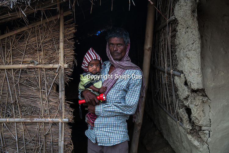 65 year old Danbar Mukhiya, holds his grand-daughter Nisha in their house in Joganiya B in Saptari, Nepal. Nisha was refered by a female health worker and was diagnosed on Feb 12, 2014. MUAC - 85 mm, Weight - 4kg, and Height - 56.5 cm.