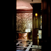 The luxurious bathroom has a free-standing copper bath and black and white marble floor