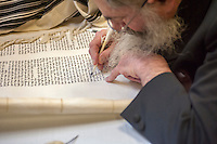 Sofer Yehuda Clapman finishes final letters the Chabad of Harlem's Sefer Torah in Harlem in New York on Sunday, October 27, 2013. The ten year old synagogue commissioned the hand-written parchment scroll (which contains 304,805 Hebrew letters) two years ago. Harlem was once home to over 200 synagogues before the Great Depression and current census records have shown that the caucasian population now outnumbers african-americans.  (© Richard B. Levine)