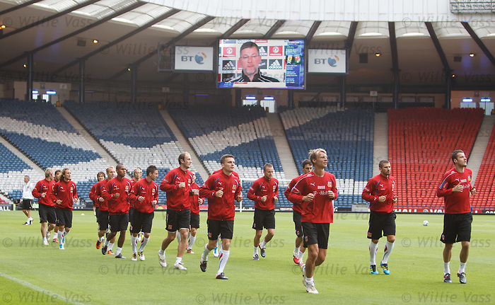Craig Levein looks down from the giant TV scoreboards on the Czech team at Hampden for training