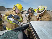 NWA Democrat-Gazette/BEN GOFF &bull; @NWABENGOFF<br /> Parker Bush (from left), Cave Springs firefighter, cousin Cooper Bush, Centerton firefighter/paramedic, and Mike Cerasale, Centerton division chief for training, conduct vehicle extrication training on Saturday Aug. 8, 2015 during a full-scale training exercise at Northwest Arkansas Regional Airport in Highfill. The exercise for agencies in Benton County that respond to emergencies at the airport simulated a plane crash scenario.