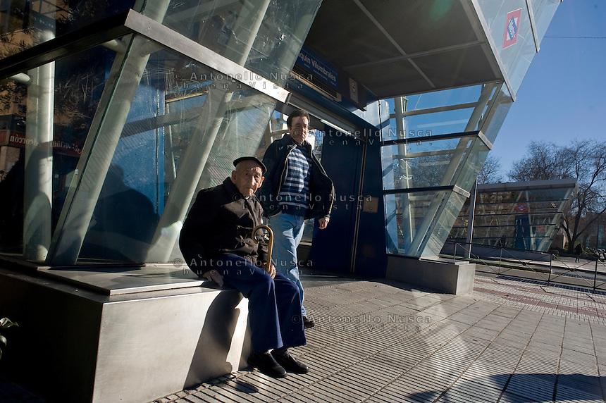Un anziano signore seduto all'ingresso di una fermata della metropolitana di Madrid.