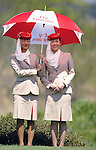 JEJU, SOUTH KOREA - APRIL 25:  Fly Emirates' hostesses hold umbrellas on the 14th hole during the Round Three of the Ballantine's Championship at Pinx Golf Club on April 25, 2010 in Jeju, South Korea. Photo by Victor Fraile / The Power of Sport Images