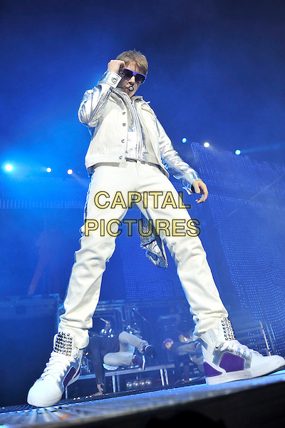 JUSTIN BIEBER.Performing live at the O2 Arena, London, England..March 17th, 2011.stage concert live gig performance music full length white jeans denim silver jacket singing sunglasses shades trainers sneakers .CAP/MAR.© Martin Harris/Capital Pictures.