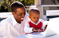 Attractive black African American father with young boy playing with computer at home in sunshine outdoors smiling and happy