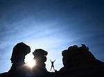 man with arms raised and jumping with sunshine surrounded by silhouetted sandstone rock formation pinnacles.  mesa de cuba, northern new mexico, usa.