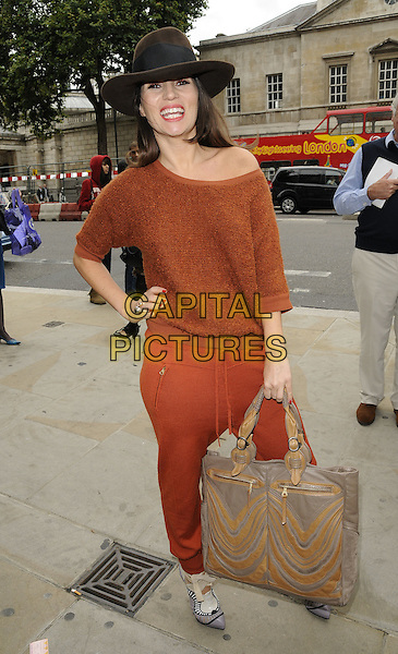 GRACE WOODWARD.The Julien MacDonald s/s 2011 fashion show, London Fashion Week, Day 3, London, England..September 19th, 2010.LFW full length black brown orange hat off the shoulder jumper sweater knitted trousers grey gray beige bag purse shoes harem hand on hip.CAP/CAN.©Can Nguyen/Capital Pictures.