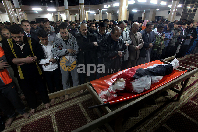 "Palestinian mourners pray next to the body of Mahmoud Zakot, 20, during his funeral in the northern Gaza Strip March 30, 2012. Israeli security forces shot dead Zakot in the Gaza Strip on Friday, medics said, and clashed with Palestinian stone-throwers around Jerusalem during ""Land Day"" rallies that turned violent. Ashraf Amra"