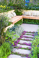 Fragrance garden: Thyme herbs in flower Thymus, in crevices and nooks and crannies of path stepping stones walkway with herbs and lettuce vegetables: rosemary Rosmarinus, Salvia officinalis, Lavandula lavender, dill, kale, patio, Garden benches with pillow cushions in edible landscape