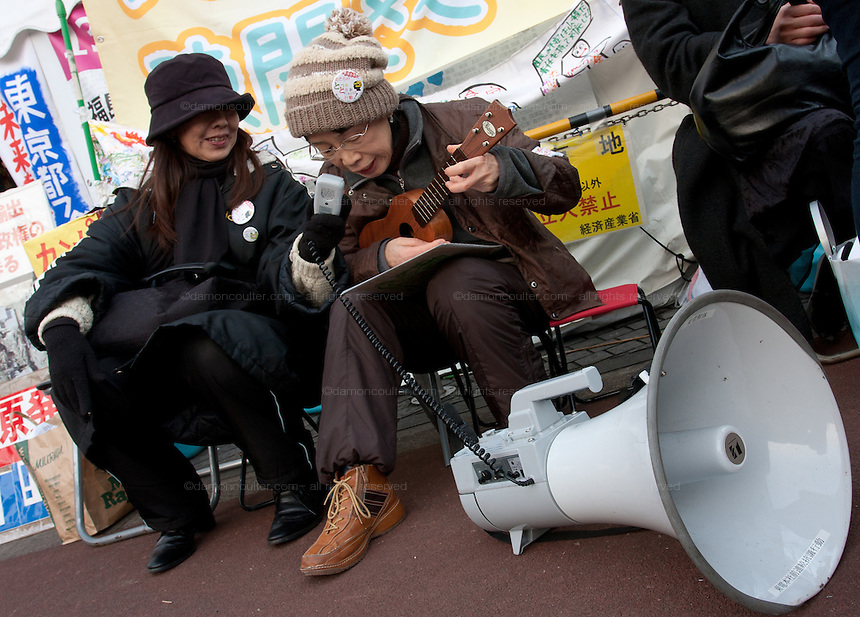 Women protesters playing music at an anti-nuclear power demo and occupy Tokyo protest outside the Ministry of the Economy, Trade and Industry (METI) in Tokyo, Japan. Friday 27th January 2012. The protest has been running from September 2011 and was scheduled for forcible eviction by police at 5pm on January 27th as the camp had been declared a fire risk by Minister Yukio Edano, with around 500 supporters and protesters turning up to resist the eviction however the camp was still in place the night of the 27th.