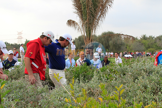 Graeme McDowell searches for Charl Schwartzel's ball in the bushes after a wayward drive on the 13th hole during Day 3 Saturday of the Abu Dhabi HSBC Golf Championship, 22nd January 2011..(Picture Eoin Clarke/www.golffile.ie)