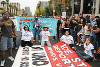 Phoenix, Arizona. April 25, 2012 - From left (on the ground): Danielle Nieto, Amy McMullen, Jovana Renteria, and Jesse Davenport, block Central Avenue as they protest against SB 1070. About 500 people protested the controversial law on the same day U.S. Supreme Court justices heard legal arguments on the Arizona vs. United States case. At the end of the march, six activists blocked Central Avenue by sitting in the middle of the street. They all were arrested by the Phoenix Police Department and taken to the Fourth Avenue County Jail. Photo by Eduardo Barraza © 2012