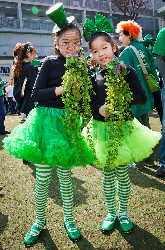 Two young Japanese girls dressed in green with bunches of Shamrocks at Tokyo`s St.Patrick`s day parade.