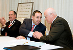 TORRINGTON, CT-121817JS07--- David Whitehead, Executive Vice President Chief Strategy and Transformation with Hartford Healthcare, left, applauds as Jeffrey Flaks, President and COO of Hartford Healthcare, center, and Daniel J. McIntyre, President & Executive Director of Charlotte Hungerford Hospital, right, shake hands following a signing ceremony that officially turnover Charlotte Hungerford Hospital to Hartford Healthcare Thursday in the Memorial Conference Hall at the hospital in Torrington <br />  Jim Shannon Republican-American