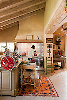 A bright red vintage meat slicer sitting on the kitchen island unit is one of the many eclectic pieces that gives this large country kitchen personality as well as functionality