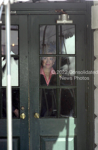 Washington, DC - December 18, 2000 -- First Lady Hillary Rodham Clinton peers through the door of the White House as she awaits the arrival of incoming First Lady Laura Bush.<br /> Credit: Ron Sachs / CNP