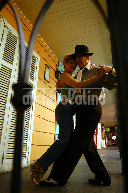 Turistas extranjeros bailan el tango con el artista Guillermo Alio en el barrio La Boca de Buenos Aires. El turismo  se incremento por la gran cantidad de fanaticos de tango de todo el mundo que llegan a la ciudad para bailar o aprender a bailar.*Foreign tourists dance tango with artist Guillermo Alio in Buenos Aires. The tourism boom is partialy fueled by tango freaks from all over the world getting to the city to dance or learn how to do it.