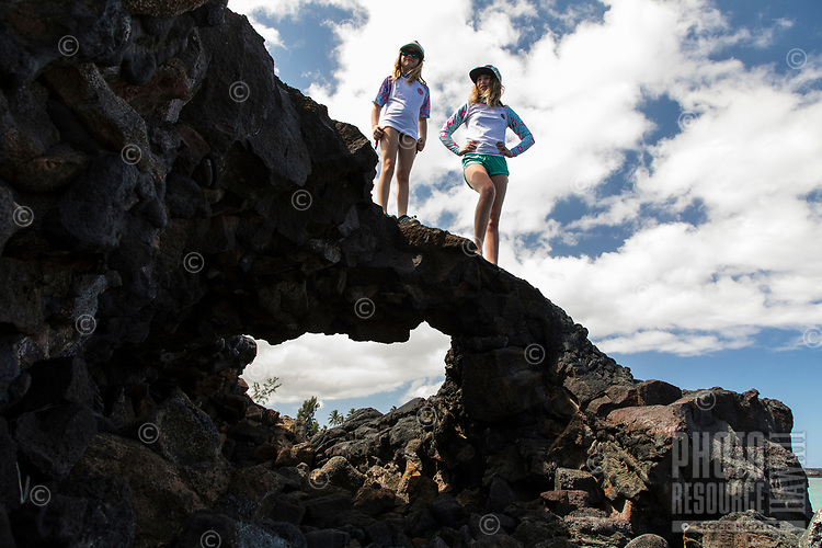Two girls take in the view from lava rocks at Kiholo Bay, a snorkeling and wildlife viewing area in Kona, Big Island.
