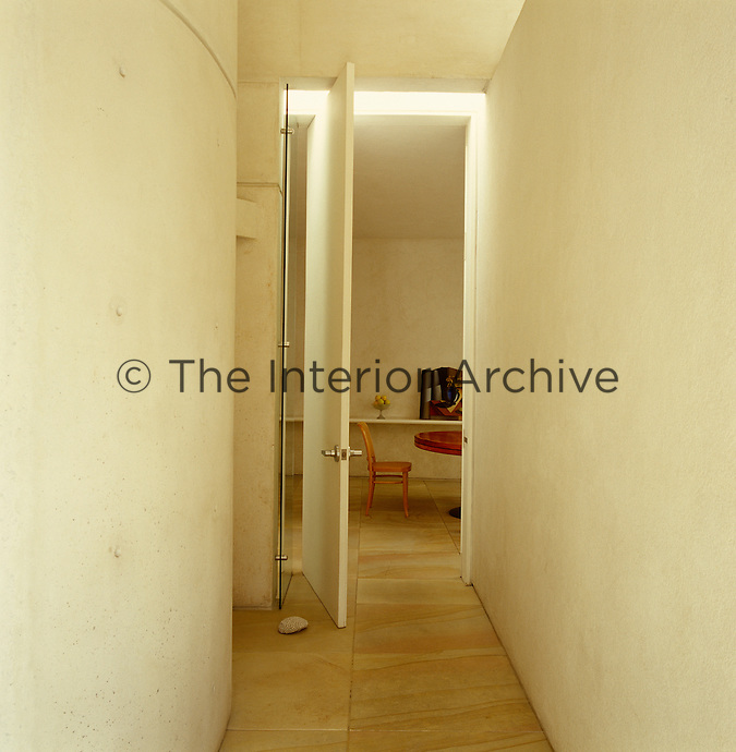 View along a corridor through a tall pivotal door into the dining room