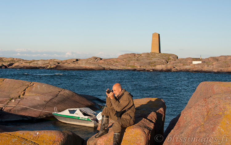 Great sunny morning! at the skerries of Segelskär Daybeacon after intense photographing at sunset, full moon, nightime and early morning hours. Photographer Fraser Bliss pauses for a brief respite in the Gulf of Finland outside Tammisaari.