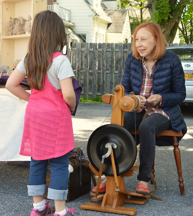 A young girl is fascinated by the handcraft spinning wheel demonstration by Mariepaule Rossur of Cottage on the Hudson Crafts, where everything is made from wool, on the Opening Day of the 2017 Saugerties Farmer's Market on Saturday, May 27, 2017. Photo by Jim Peppler. Copyright/Jim Peppler-2017.