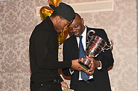 Kheron Gilpin (L) of Miguel's ABC receives the Pat Floyd Cup for best London amateur boxer from James Cook during the London Ex-Boxers Association Awards Lunch at the Grand Connaught Rooms on 16th February 2020