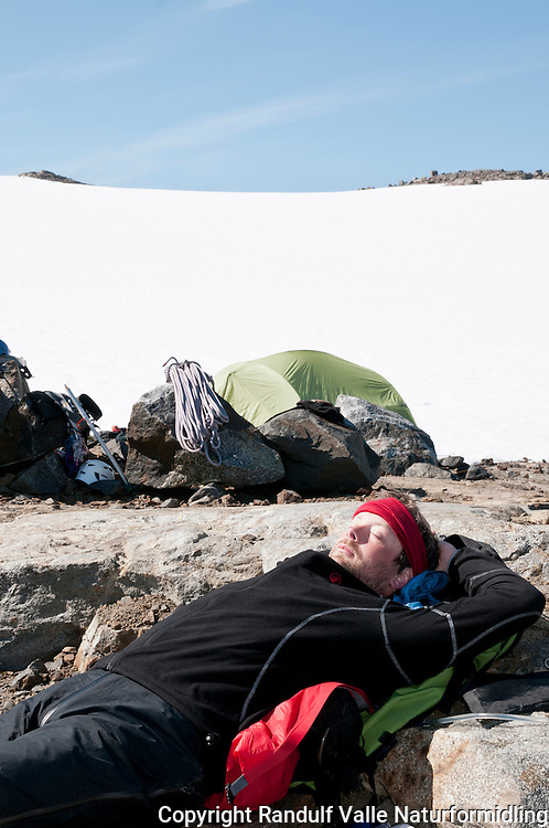 Mann slapper av i leir på en barflekk rett ved fronten av Nordmannsjøkulen på Seiland. ---- Man relaxing in camp, just beside the glacier Nordmannsjøkulen on Seiland.