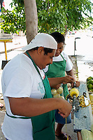 Man using a mango peeling machine at his fruit stand on Avenida Tulum in downtown, Cancun, Quintana Roo, Mexico.