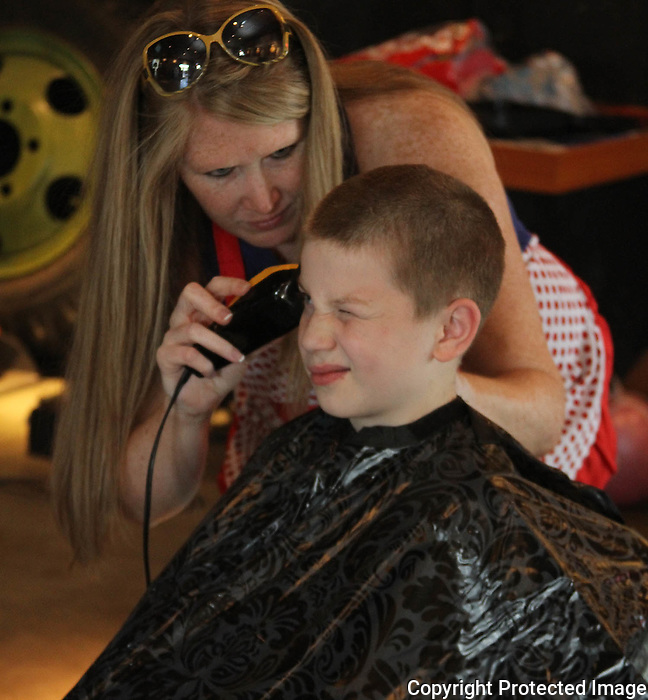 Zackary Pierce has his hair cut by Jennifer Fox of the Buzz-off for cancer at the Holbrook American Legion on Saturday June 14, 2015. (Photo by Gary Wilcox)