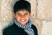 A young boy in Jerusalem wears a keffiyeh wrapped around his shoulders. The black and white headdress, traditionally worn by Palestinian farmers has become a symbol of Palestinian identity and worn by Palestinian men of every rank and age.