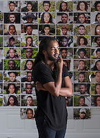 Cruz Riley '17 stands before photos he took of other students for his project, The Ninety-Five. His project presented color portraits of black students at Occidental College in clusters of five, dispersed at 19 locations all over campus. Photographed July 14, 2016 in the Weingart Hall Gallery for Occidental Magazine.<br /> (Photo by Marc Campos, Occidental College Photographer)