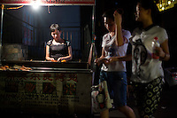 Dong Ping Chun barbecues chicken and corn at a stand near the B District Middle Gate of Chongqing University in the Shapingba district of Chongqing, China. She and her husband, who live nearby, have run the stand for 13 years, and often serve food until 2am. This close to the university, most of her customers are students. She serves 6 cuts of chicken, but wings and legs are the most popular. The meat is barecued with a sauce that is very similar to some American barbecue sauces, sweet, tangy, and spicy.