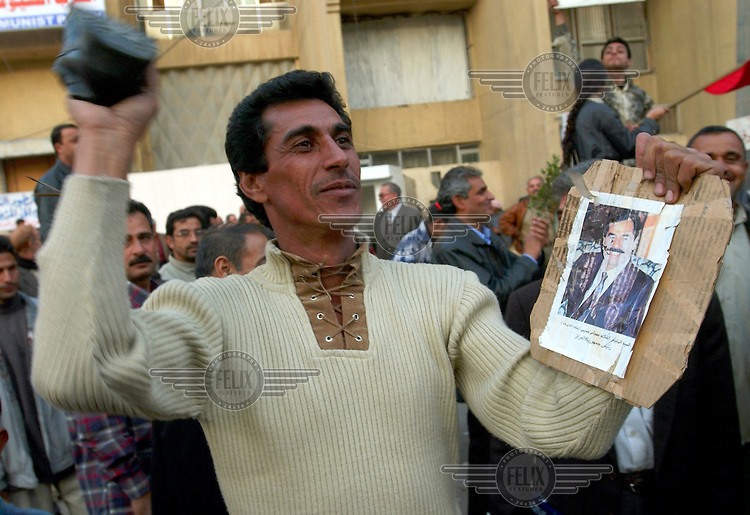A man slams his shoe on a portrait of Saddam Hussein, following the news that the ex-President had been captured by American forces.