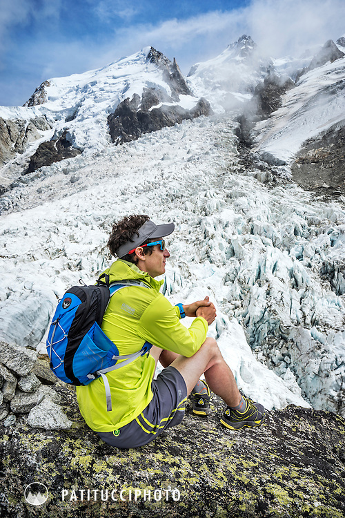 Trail running along the Bossons Glacier, beneath the Aiguille du Midi and Mont Blanc. Chamonix, France. The runner is stopped and sitting to look out on the glaciers next to the trail.