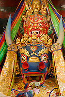 Protector deities of the Gelugpa order, Dorje Jigje, blue bull's head festooned with skulls, red Hayagriva, and White Tara with eye in forehead, in chapel at Ngagpa College, Drepung Monastery, Lhasa, Tibet, China.