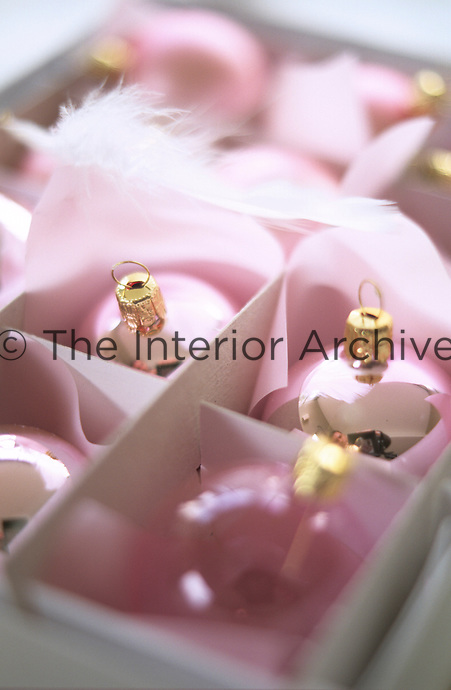 Pink metallic Christmas baubles packed in a box lined with pink tissue paper