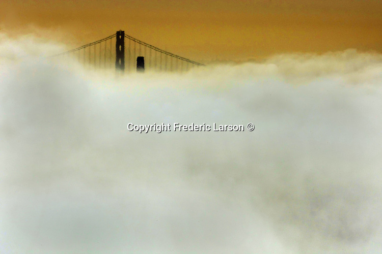 The incoming fog blankets San Francisco skyline where only the top of the Bay Bridge and Coit tower at sunrise are visible from the Marin  headlands in Sausalito, California.
