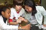 Elementary or Middle School Grade 6 science class DNA extraction two female and one male student working together horizontal