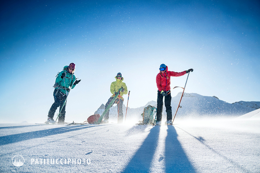 A group of ski tourers putting their skins on in windy weather while on a ski tour of the Berner Haute Route, Switzerland