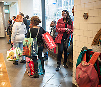 A shopper loaded with her purchases from off-price retailers T. J. Maxx and Burlington in a fast food restaurant in Midtown Manhattan in New York on Saturday, March 25, 2017.  (© Richard B. Levine)